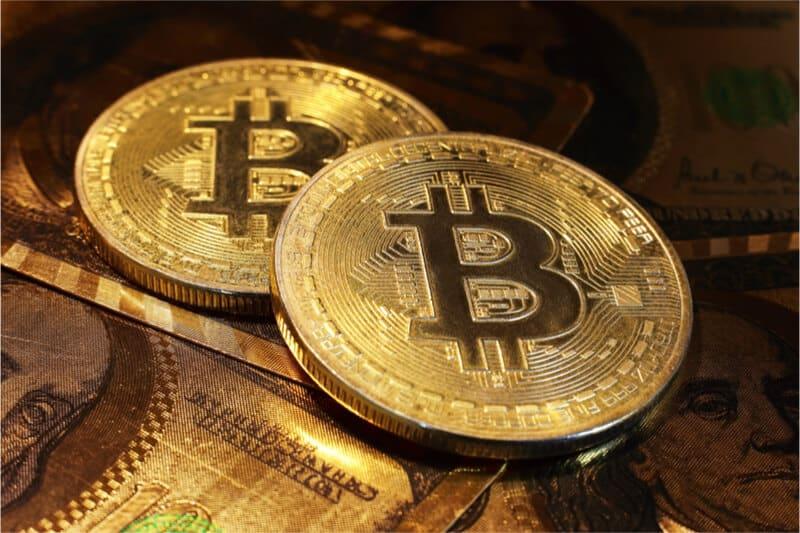 Goldene Bitcoins mit Dollarscheine im Hintergrund