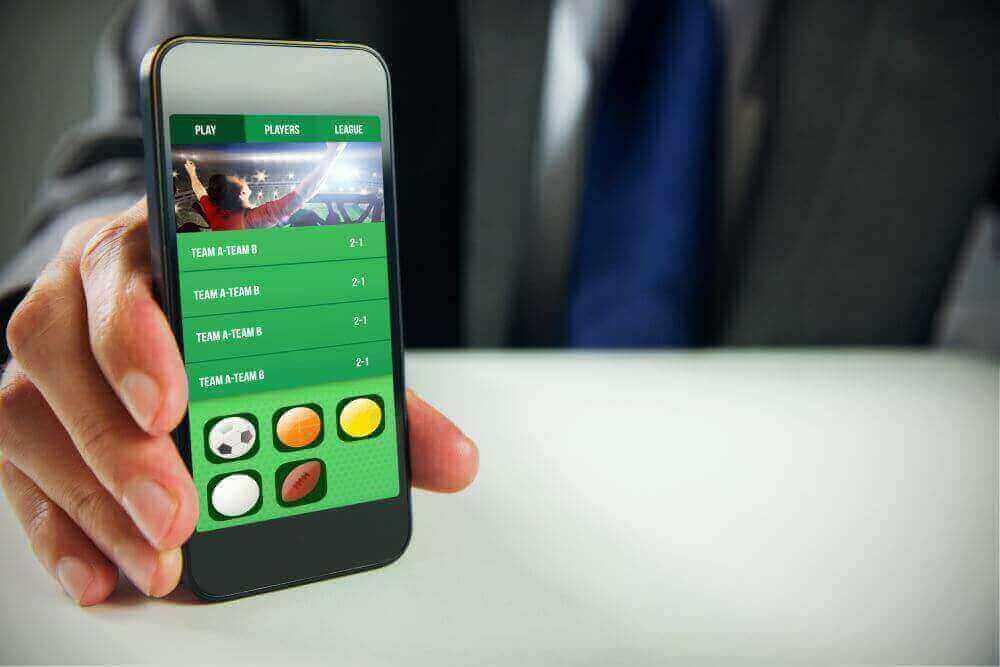 Mann benutzt Smartphone für Sportwetten