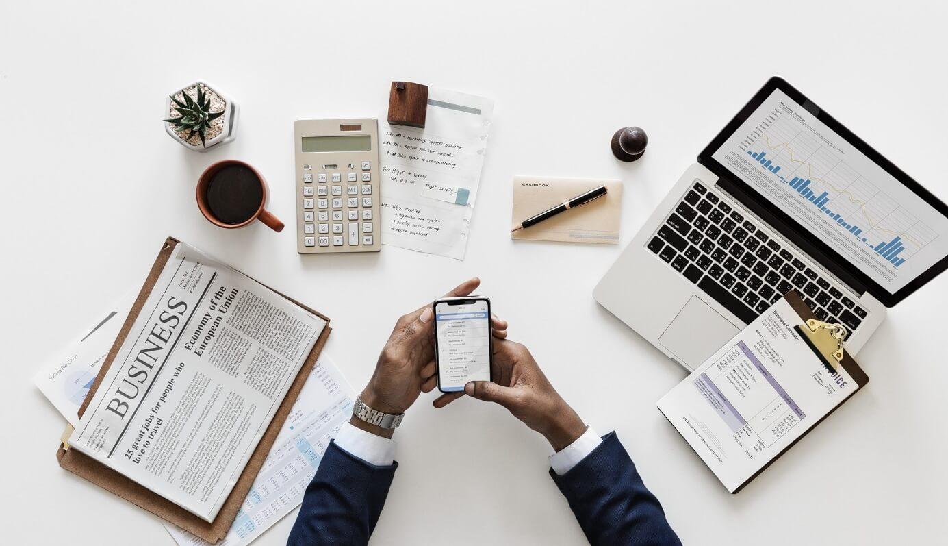 Weißer Schreibtisch von oben mit Dokumenten, Zeitung, Taschenrechner, Kaffeetasse und Laptop