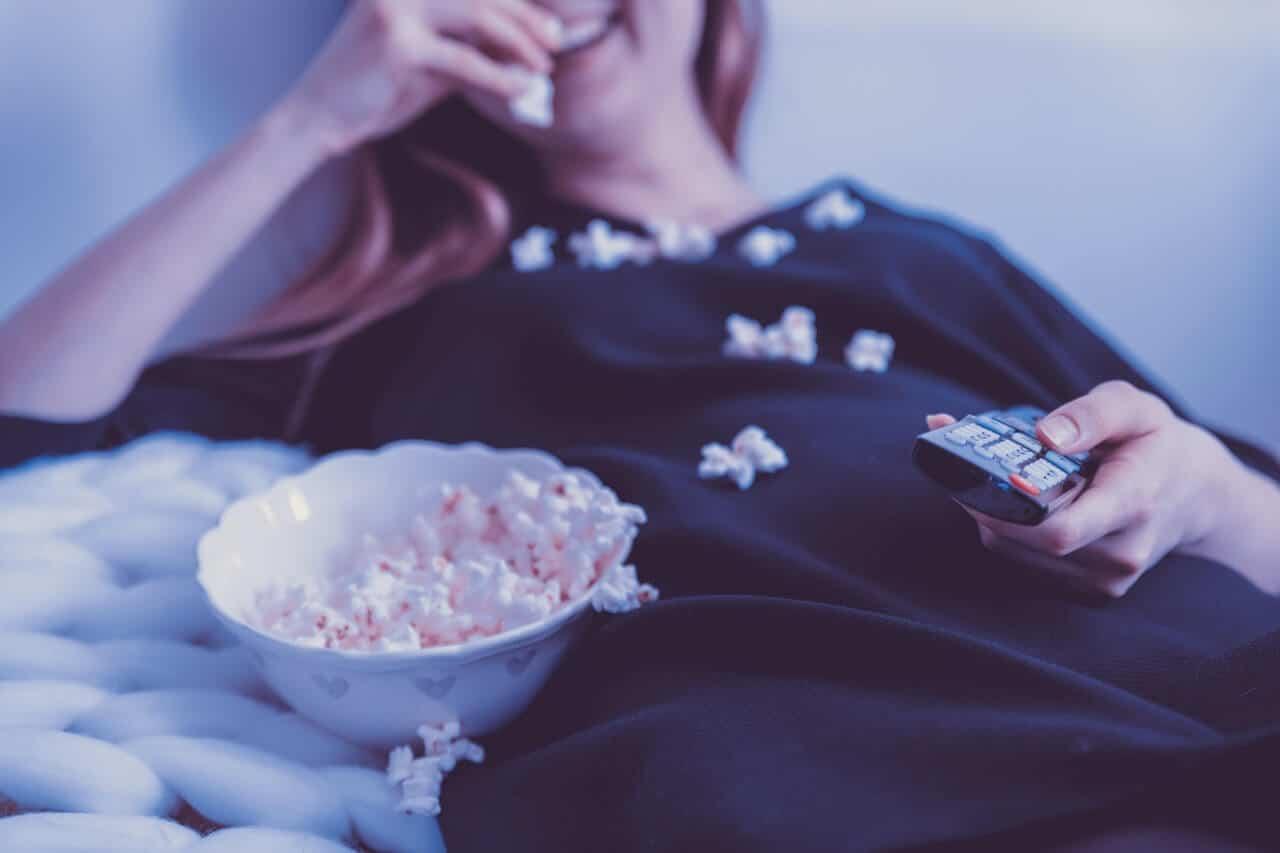 woman-wearing-black-dress-shirt-eating-popcorn-1040159
